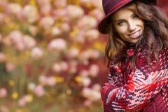 外套的妇女有帽子的和围巾在秋天停放 库存照片