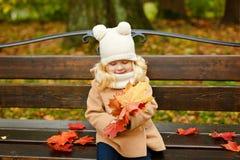 外套的小逗人喜爱的蓬松白肤金发的女孩坐在t的一条长凳 免版税库存图片