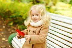 外套的小逗人喜爱的蓬松白肤金发的女孩坐在t的一条长凳 免版税图库摄影