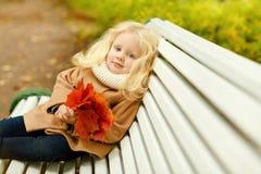 外套的小逗人喜爱的蓬松白肤金发的女孩坐在t的一条长凳 库存照片