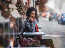 外套的愉快的非裔美国人的女孩在steet咖啡馆 库存图片