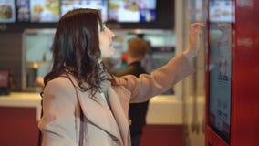 外套的美丽的深色的妇女通过终端点食物 影视素材