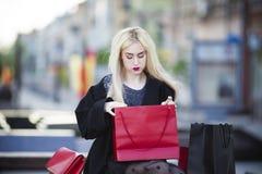 黑外套的美丽的年轻时髦的白肤金发的妇女有购物袋的坐一条长凳在公园 免版税图库摄影