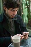 外套的年轻英俊的人用发短信在手机的咖啡 库存照片