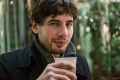 外套的年轻英俊的人用看照相机的咖啡 库存照片