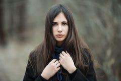 黑外套蓝色围巾关闭的年轻美丽的女孩在秋天/春天森林公园 有华美前的一个典雅的深色的女孩 库存照片