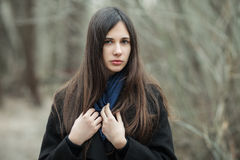 黑外套蓝色围巾关闭的年轻美丽的女孩在秋天/春天森林公园 有华美前的一个典雅的深色的女孩 图库摄影