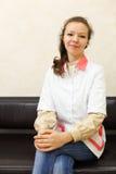 外套长沙发加工好的女孩坐白色 免版税库存图片