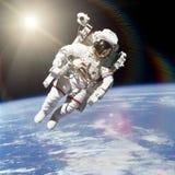外层空间的宇航员在地球的背景 免版税库存图片