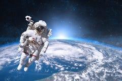 外层空间的宇航员在地球的背景 图库摄影