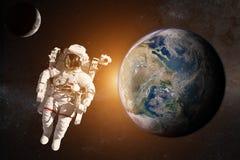 外层空间的宇航员在地球的背景 免版税库存照片