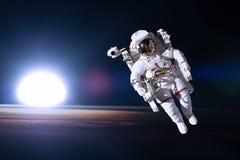 外层空间的宇航员在夜地球的背景 图库摄影