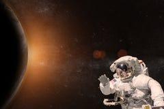 外层空间的宇航员在行星的背景 库存图片