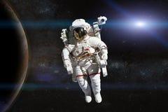 外层空间的宇航员在行星的背景 免版税库存图片