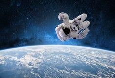 外层空间的宇航员与作为背景的行星地球 要素 免版税库存照片