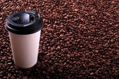 外带的一次性咖啡杯有烤豆背景 免版税库存图片