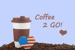 外带的陶瓷杯子和咖啡豆在蓝色背景 免版税图库摄影