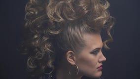 外形炸毁在从她的高发型,关闭的垂悬的卷毛的射击了年轻女人  影视素材