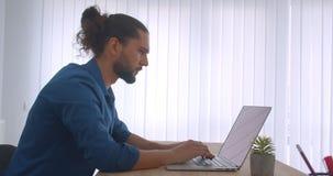 外形被射击与马尾辫工作的进步商人与膝上型计算机在轻的办公室 影视素材