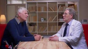 外形被射击老人有与医生的一个任命在白色外套谈话在书架背景 影视素材
