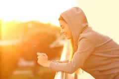 外形青少年使用一个巧妙的电话在阳台上 库存图片