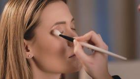 外形,化妆师在眼皮上把暗影,在一个白种人金发碧眼的女人的面孔的专业白色刷子放 股票视频