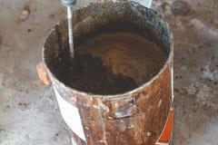 外来工人大师揉膏药的灰浆 金属桶 自然过程 r 库存图片