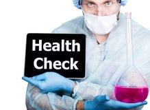 外科制服的医生,拿着桃红色烧瓶和数字式片剂个人计算机有身体检查标志的 互联网技术和 免版税库存图片