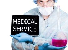 外科制服的医生,拿着桃红色烧瓶和数字式片剂个人计算机有医疗服务标志的 互联网技术和 免版税库存图片
