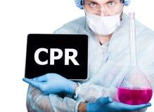 外科制服的医生,拿着桃红色烧瓶和数字式片剂个人计算机有cpr标志的 互联网技术和网络 免版税库存照片