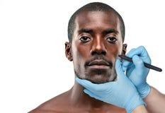 外科医生在男性面孔的图画标记反对灰色背景 概念查出的整容手术白色 图库摄影