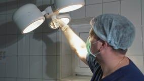 外科医生拉扯一个强有力的光源为了为操作做准备 医生为手术做准备一张桌和医疗 股票视频