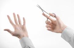 外科和医疗题材:在拿着外科钳位剪刀的一件白色实验室外套的医生的手被隔绝在白色背景 库存图片
