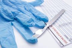 外科手套、解剖刀和血液学验血在手术台上收效 手术或它的完成的准备 医师 免版税库存照片