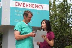 外科医生、医生、医师,临床工作者和亚洲护士佩带洗刷在医院急诊室标志前面的立场 免版税库存图片