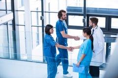 外科医生、医生和护士与彼此握手 免版税库存照片