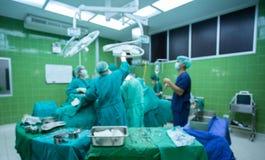 外科医生在外科手术室合作与患者一起使用监视  库存图片