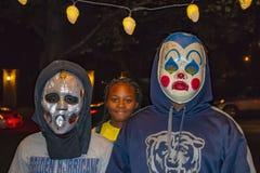 外籍人和墨西哥Lucha libre搏斗的面具的两个男孩等待与小女孩的万圣夜糖果有大微笑等待的behin的 免版税库存照片