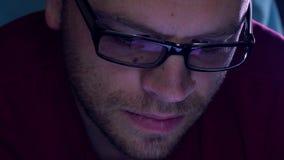 黑外缘玻璃的英俊的有胡子的年轻人使用他的片剂计算机在暗室 紫色屏幕焕发 免版税图库摄影