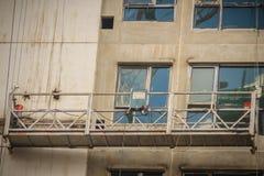 外部工作的暂停的摇篮在喂上升楼房建筑 外在repai的长平底船推力或阶段脚手架 库存图片