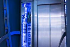外部是玻璃悬墙电梯,蓝色口气图 免版税库存照片