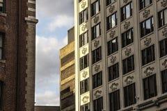 外部艺术装饰初步现代化的办公楼门面在有装饰漩涡花饰的城市 免版税库存照片