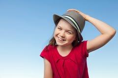 外部逗人喜爱的小女孩戴一件红色衬衣和帽子 免版税图库摄影