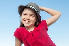 外部逗人喜爱的小女孩戴一件红色衬衣和帽子 免版税库存照片