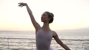 外面优美的芭蕾舞女演员跳舞芭蕾元素与背景的海 在白色芭蕾舞短裙的白种人跳芭蕾舞者 股票录像