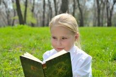 外面可爱的逗人喜爱的小女孩阅读书 免版税库存图片