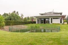 外面大房子和池塘 免版税库存图片