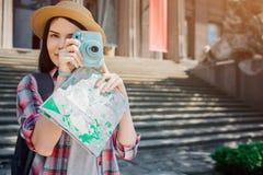 外面好和可爱的深色的立场 旅行家举行蓝色照相机和姿势 并且她有地图在手 15个妇女年轻人 免版税库存图片