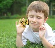 外面小男孩传染性的春天蝴蝶 免版税库存照片
