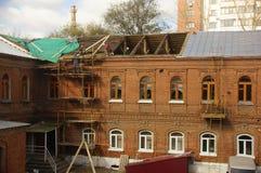 外面砖房子屋顶、顶楼、屋顶窗口和房檐的屋顶建筑 免版税库存照片